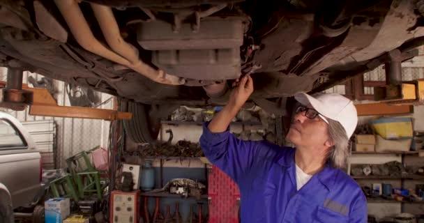 Muž auto mechanik kontroluje způsob podvozek auta v garáži.