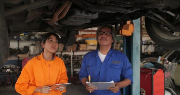 Professional mechanic team using digital tablet while working under lifted car.