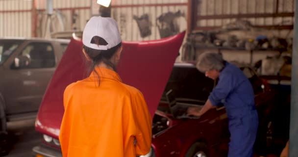 Portrait of a young beautiful car mechanic in a car workshop.