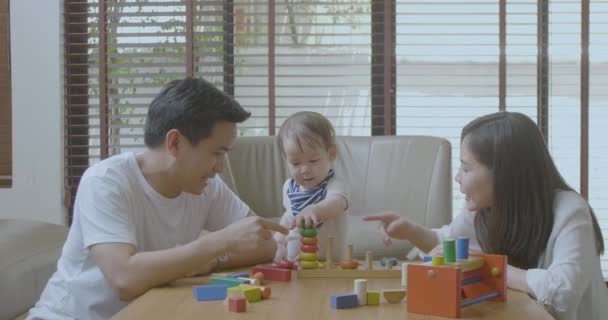 Happy mother, father and little asian boy playing with wooden toy blocks at home