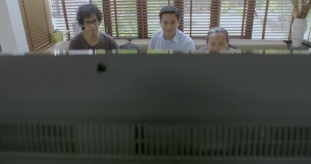 Group of asian flat mates watching sports competition on TV at home.