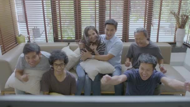 Gruppe der asiatischen Wohnung paart sich gerade sportlichen Wettkampf im Fernsehen zu Hause
