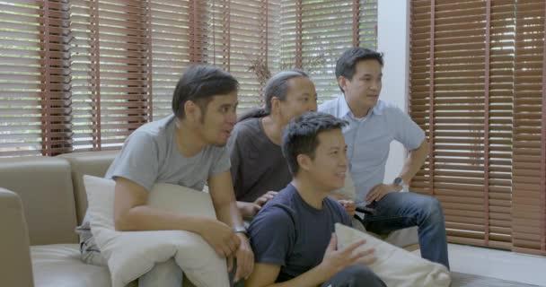 Gruppe asiatischer Mitbewohner schaut Sportwettkämpfe zu Hause im Fernsehen.