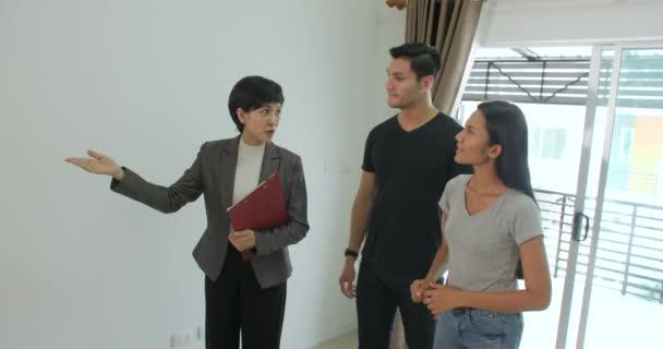 Profesionální realitní makléř ukazuje moderní dům pro mladý pár