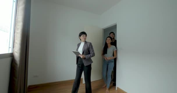Profesionální realitní makléř ukazuje moderní dům pro mladý pár.