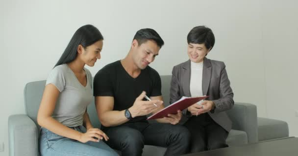 Young attractive couple meeting real-estate agent, signing contract with female broker.