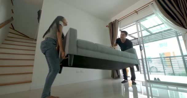 Happy young asian couple moving a sofa during their move into new house