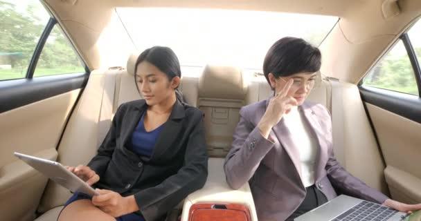 Dvě mladé podnikatelky s počítačem tablet a notebook v sedadle automobilu