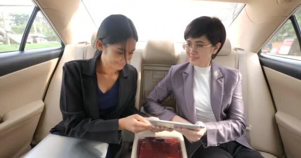 Dvě podnikatelka spolu sedí v sedadle auta s digitálním tabletu a mluví.