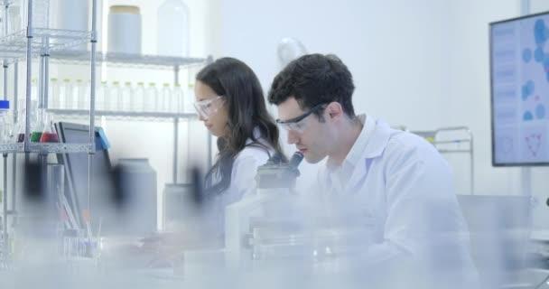 Dolly záběr z lékařského výzkumu vědci týmová práce na moderních laboratorních experimentů vědci vedení pracuje na počítačích, při pohledu na látce pod mikroskopem