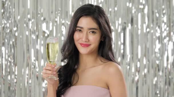 Gyönyörű ázsiai nő gazdaság pohár pezsgő konfetti között tánc.