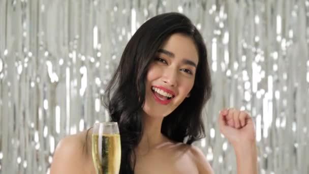 Gyönyörű ázsiai nő gazdaság pohár pezsgő konfetti között tánc