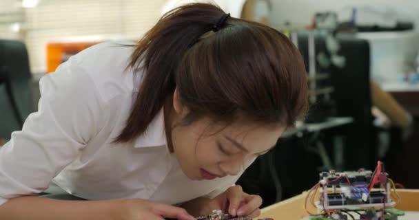 Ženské elektrotechnický inženýr pracuje s robotem, stavba, oprava robotiky v dílně