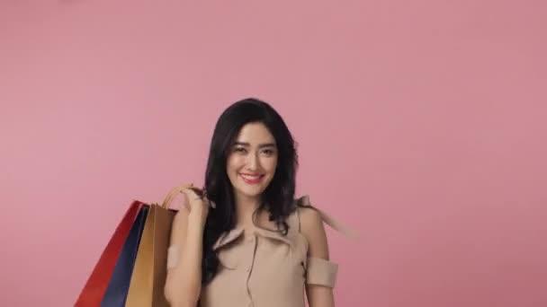 Šťastná žena drží hodně barevné tašky