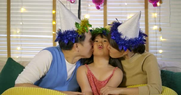 Matka a otec líbat jejich dceru s láskou. Šťastná rodina těší čas společně