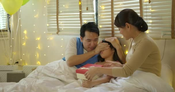 Happy asian family celebrating daughters birthday opening gifts and rejoice on bed.