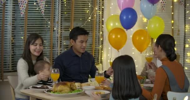 Asijská rodina těší vánoční večeři společně doma.