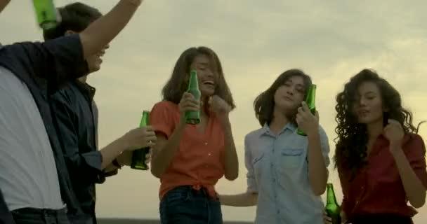 Tánc és a szórakozás ünnepelni a pirítóst, és emeli a nyári tetőtéri szemüveg csengő fiatal baráti party naplemente háttérben. Lassú mozgás