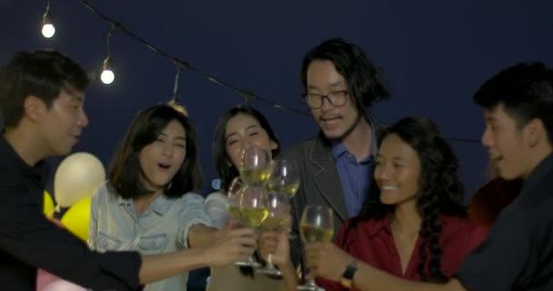 Gruppo di giovani amici ballare e divertirsi festeggiare con pane tostato e tintinnio alzando bicchieri alla festa estiva sul tetto.