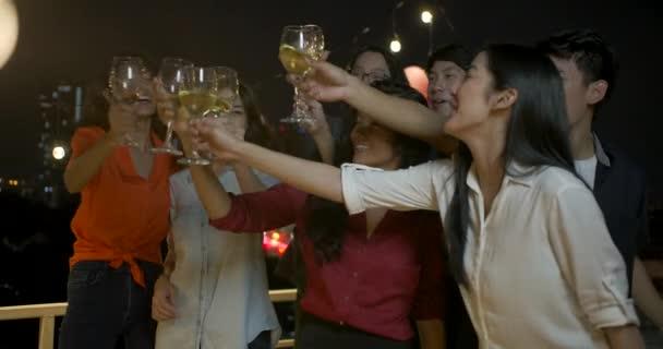 Gruppe junger Freunde, tanzen und Spaß haben mit Toast und Klirren der Gläser beim Sommerfest auf dem Dach anheben zu feiern.