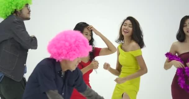 Csoport fiatal ázsiai birtoklás móka, mint egy őrült tánc a fehér háttér előtt. Emberek párt, ünneplés, élvezet és újév koncepció.