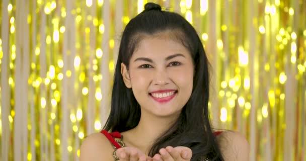 Gyönyörű ázsiai nő csillogó konfetti, vagy darab ezüst fólia fényes vibrálás függöny háttér előtt fúj