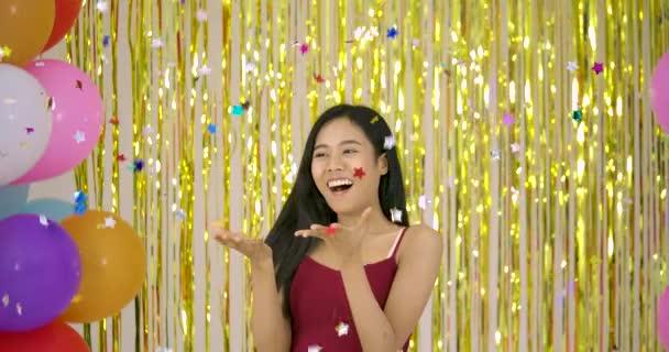 Gyönyörű ázsiai nő a konfetti nyílik arany csillogó háttér.