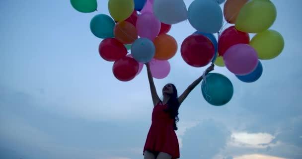 Dívka drží balon s pozadí oblohy.