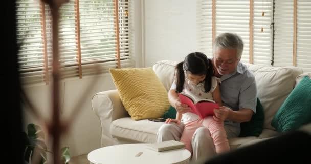 Asijské starší dědeček s malou vnučkou čtení knihy společně doma