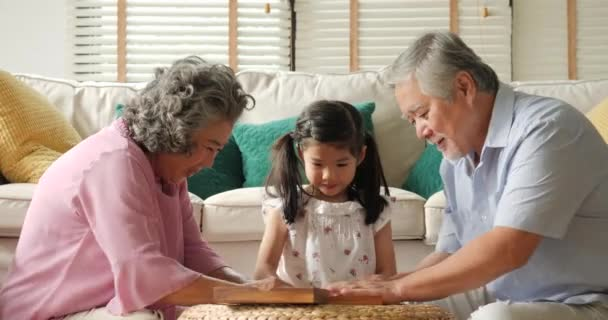 Asian senior couple playing together with a little girl at home.