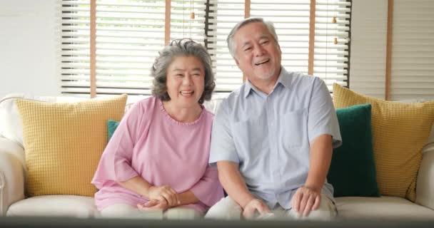 Šťastný pár senior se dívat na televizi dohromady.