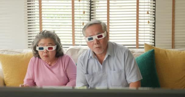 Asijské starší pár 3d brýle pro sledovat film s vzbudit emoce v obýváku.