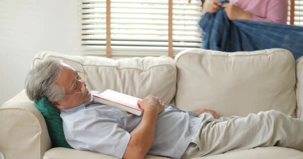 Senior man sleeping with book on the sofa in living room and his wife put  blanket on him.