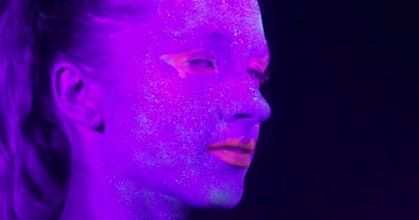 Closeup žena tvář s fluorescenční make-upu, kreativní make-up vypadat skvěle pro noční kluby.