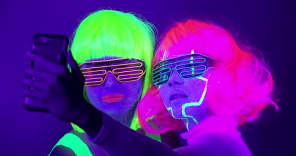 Slow motin of beautiful sexy women with fluorescent make-up and clothing taking selfie photo in neon light.