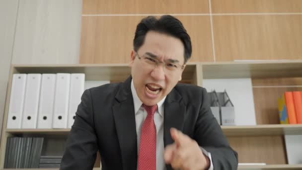 Angry businessman scolding and yelling at camera in Office.