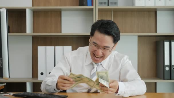 Slow motion portrait of successful asian man rejoices money. Manager enjoying dollars. Clerk sniffing new money.