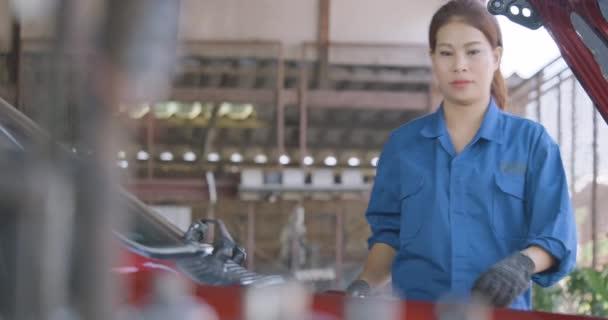 Szakmai nő szerelő javítás egy autó a garázsban.