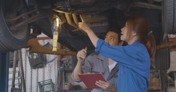 Profesionální mechanik týmu pracující pod zvednuté auto na auto opravna.