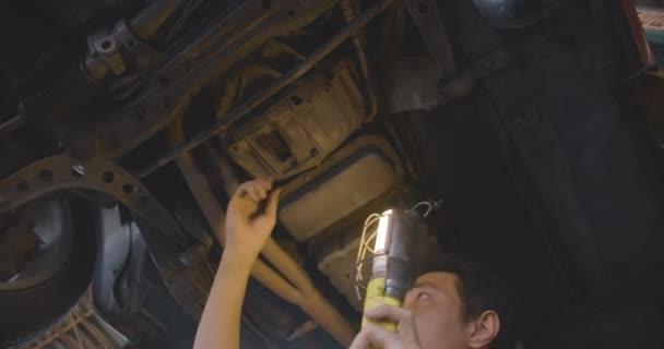 Felemelt autót auto javítóműhely alatt dolgozó hivatásos férfi szerelő.