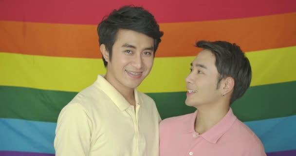 Portrét mladé asijské gay páru pózuje před gay hrdosti Duhová vlajka