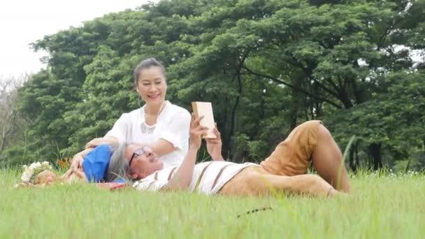 Idősebb házaspár, a férj és a feleség csinál piknik a parkban pihen a boldog érzelem.