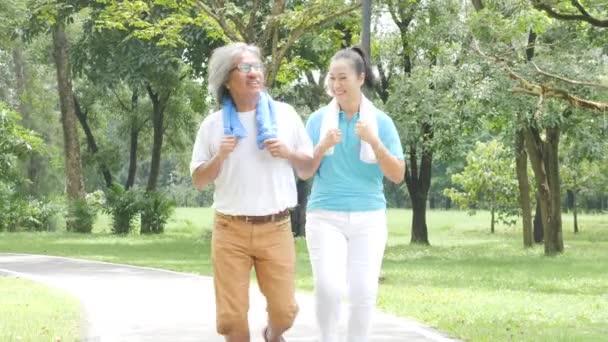 Asijské starší pár běhání v sunny garden