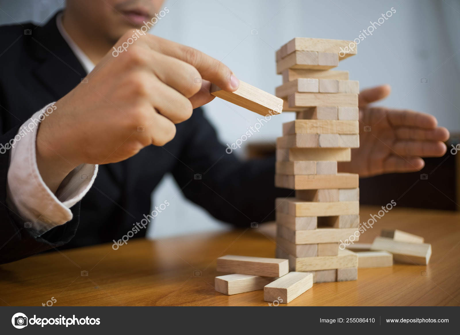 Businessmen Picking Wood Blocks To Fill The Missing Dominos And