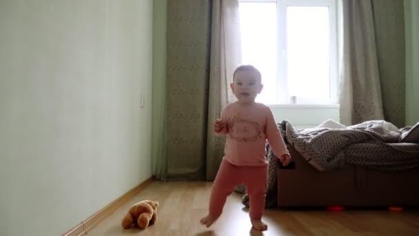 První krůčky od batole se učí chodit v obýváku. Padající a stojící nahoře