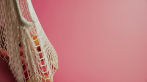 Sada plastových kuchyňských nástrojů na růžovém podkladu, šetrných k životnímu prostředí