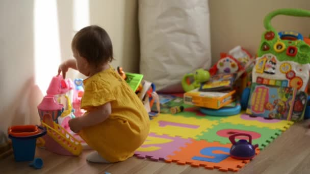 Little girl in yelow dress sits on the floor and plays with toys. Daycare or home nursery
