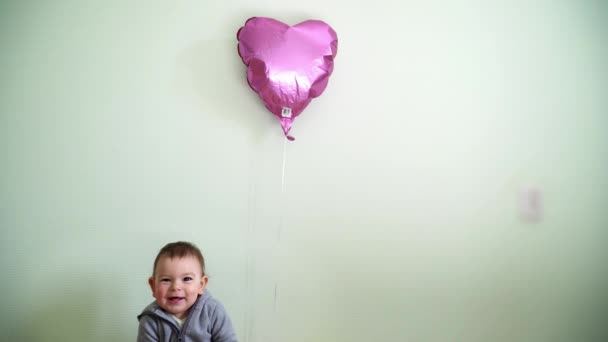 A little one year old toddler sitting near pink heart balloon. Birthday party