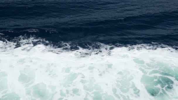Mořská temně modrá voda s bílou pěnou. Letecký pohled. Lodní vlny. Pozadí přírody