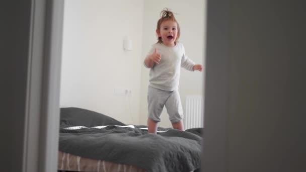 Kleinkind Mädchen springt auf dem Bett im weißen Schlafzimmer. Glückliche Gefühle, Energiekind.